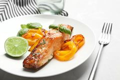 Tasty cooked salmon with vegetables on plate. Closeup Stock Image
