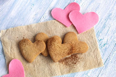 Tasty cookies, felted hearts on shabby background Stock Photography