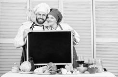 Tasty cooking class. Couple of man and woman giving ok sign at blackboard in cooking school. Master cook and prep cook stock images