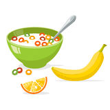 Tasty cornflakes in green bowl with spoon and banana and orange. Stock Images