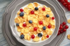 Tasty cornflakes with red currant and blueberries. On gray wooden background royalty free stock images