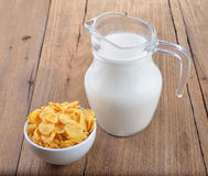 Tasty cornflakes in white  bowl and glass of milk Royalty Free Stock Images