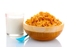 Tasty cornflakes in wooden bowl and glass of milk Royalty Free Stock Image