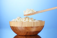 Tasty cottage cheese in bowl and spoon Royalty Free Stock Images
