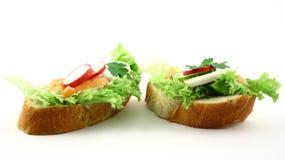Tasty couple. Couple of fresh tasty salmon's sandwiches on the white background Royalty Free Stock Photos