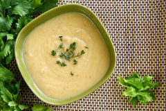 Tasty cream of celeriac soup in a green bowl. Hot cream of celeriac soup in a green bowl on the table with fresh thymus and celery. Best for autumn cold and bad Stock Photos