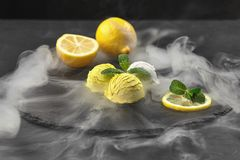 Tasty creamy and citrus lemon ice cream decorated with mint served on a stone slate over a black background. Delicious creamy and citrus lemon ice cream royalty free stock images