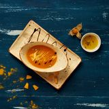 Tasty creamy pumpkin soup in oval bowl. And rectangular plate standing on blue aged wooden table. Appetizing restaurant vegan meal served with bread slices Royalty Free Stock Photo