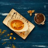 Tasty creamy pumpkin soup in oval bowl. And rectangular plate standing on blue aged wooden table. Appetizing restaurant vegan meal served with bread slices Royalty Free Stock Photography