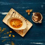 Tasty creamy pumpkin soup in oval bowl. And rectangular plate standing on blue aged wooden table. Appetizing restaurant vegan meal served with bread slices Royalty Free Stock Image
