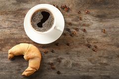 Tasty crescent roll and cup of coffee. On wooden background Royalty Free Stock Photo