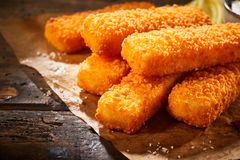 Close up view of crispy fried fish fingers. Tasty crispy deep fried fish fingers in close up view on table Royalty Free Stock Images