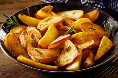 Tasty crispy fried wedges of potato with rosemary royalty free stock image