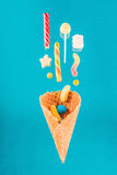 Tasty crispy waffle cone and mix of delicious sweets on blue Royalty Free Stock Photography