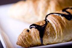 Tasty croissant. Croissant with some chocolate and stwawberry sauce Royalty Free Stock Photos
