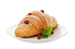 Tasty croissant with sugar powder and berrie. S on plate against white background royalty free stock photo