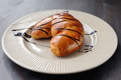 Tasty croissant on the white plate. Fresh and tasty croissant on the white plate Royalty Free Stock Photography