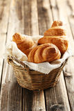 Tasty croissants. In basket on brown wooden background Royalty Free Stock Photography