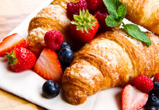 tasty croissants with berries on wooden background Royalty Free Stock Photography