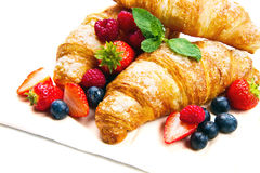 Tasty croissants with berries on wooden background Royalty Free Stock Photo