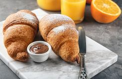 Tasty croissants with chocolate sauce. On marble board stock photo