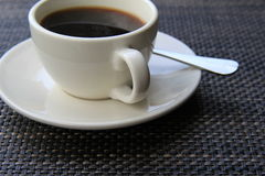 Tasty cup of steaming coffee on patterned placemat Royalty Free Stock Images