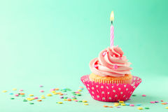 Tasty cupcake with candle on a green background Royalty Free Stock Images