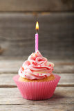 Tasty cupcake with candle on the grey wooden background Royalty Free Stock Photo