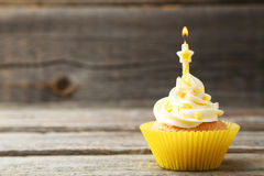 Tasty cupcake with candle on a grey wooden background Stock Images