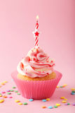 Tasty cupcake with candle on the pink background Royalty Free Stock Photography