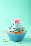 Tasty cupcake on the green background Stock Image