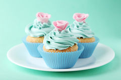 Tasty cupcake on plate on the green background Stock Image