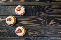 Tasty cupcake with strawberry on dark wooden background. Strawberry cupcakes on wooden background. Tasty cupcake with strawberry on dark wooden background Stock Images