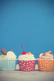 Tasty cupcake on wooden table. On blue background with copy space for write text Stock Photography