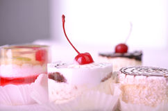 Tasty cupcakes on grey background. Small cake on a white background with blurry small cake with berries and jelly Stock Images