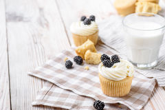 Tasty cupcakes on a white wooden table. Vanilla cupcakes on a checkered cloth Stock Images