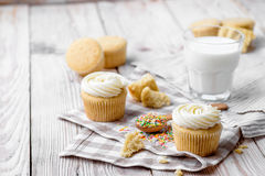 Tasty cupcakes on a white wooden table. Vanilla cupcakes on a checkered cloth Horizontal Stock Image