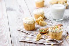 Tasty cupcakes on a white wooden table. Vanilla cupcakes on a checkered napkin Horizontal Royalty Free Stock Photos
