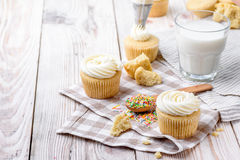 Tasty cupcakes on a white wooden table. Vanilla cupcakes on a checkered napkin Horizontal Royalty Free Stock Photo