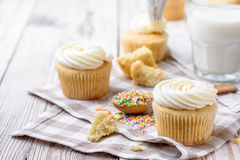 Tasty cupcakes on a white wooden table. Vanilla cupcakes on a checkered napkin Horizontal Stock Images
