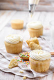 Tasty cupcakes on a white wooden table. Vanilla cupcakes on a checkered napkin Vertical Royalty Free Stock Photo