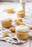 Tasty cupcakes on a white wooden table. Vanilla cupcakes on a checkered napkin Vertical Royalty Free Stock Photos