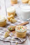 Tasty cupcakes on a white wooden table. Vanilla cupcakes on a checkered napkin Vertical Stock Photos