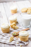 Tasty cupcakes on a white wooden table. Vanilla cupcakes on a checkered napkin Vertical Royalty Free Stock Image