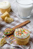Tasty cupcakes on a white wooden table. Vanilla cupcakes on a checkered napkin Vertical Stock Image