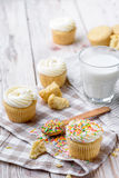 Tasty cupcakes on a white wooden table. Vanilla cupcakes on a checkered napkin Vertical Stock Images