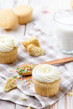 Tasty cupcakes on a white wooden table. Vanilla cupcakes on a checkered napkin Vertical Royalty Free Stock Images