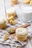 Tasty cupcakes on a white wooden table. Vanilla cupcakes on a checkered napkin Vertical Stock Photography