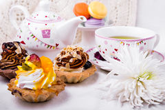 Tasty and delicious cake with cup of green tea on white tablecloth Stock Image