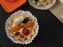 Two sand air cream, berries and nuts cakes and orange figure royalty free stock photography